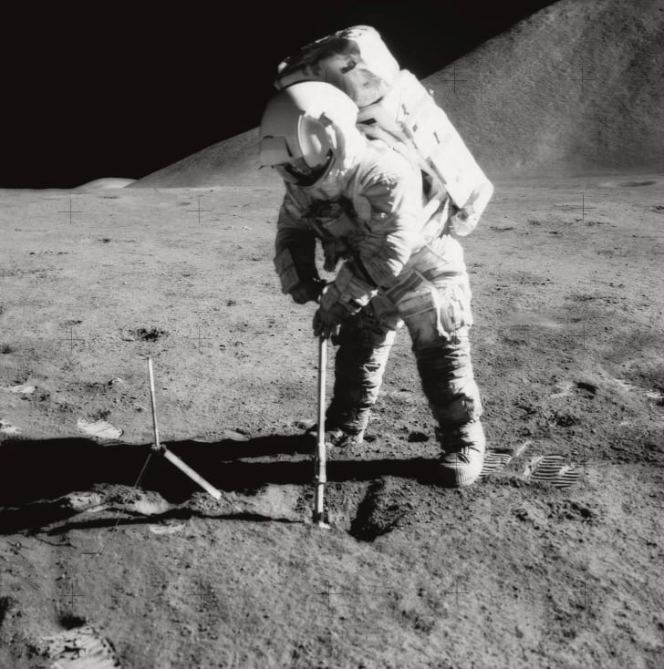 Astronaut James B. Irwin, lunar module pilot, uses a scoop in making a trench in the lunar soil during Apollo 15 extravehicular activity (EVA). Mount Hadley rises approximately 14,765 feet (about 4,500 meters) above the plain in the background