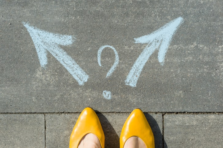 Feet in yellow heels in front of two arrows and a question mark drawn in chalk on the sidewalk