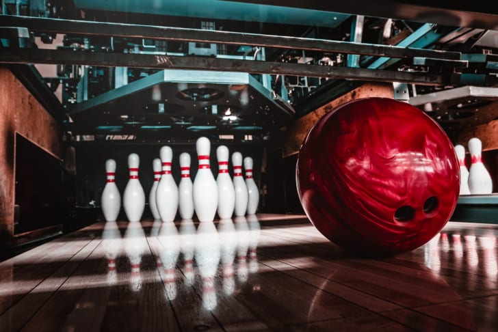 A red bowling ball resting in front of ten bowling pins on a lane