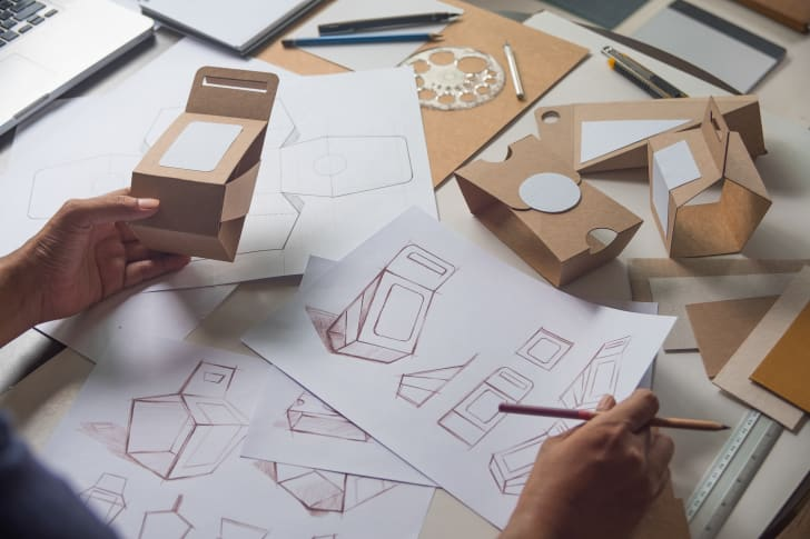 The hands of a designer over sketches of a cardboard gift box, holding one box