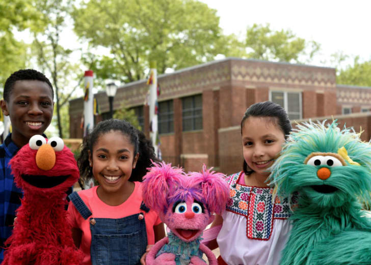 Elmo, Abby Cadabby, and Rosita (L-R) pose with fans of 'Sesame Street'