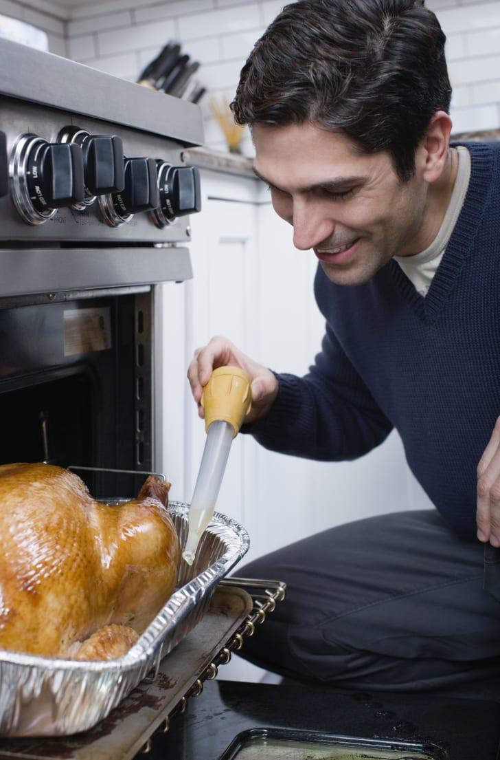 Man basting a turkey