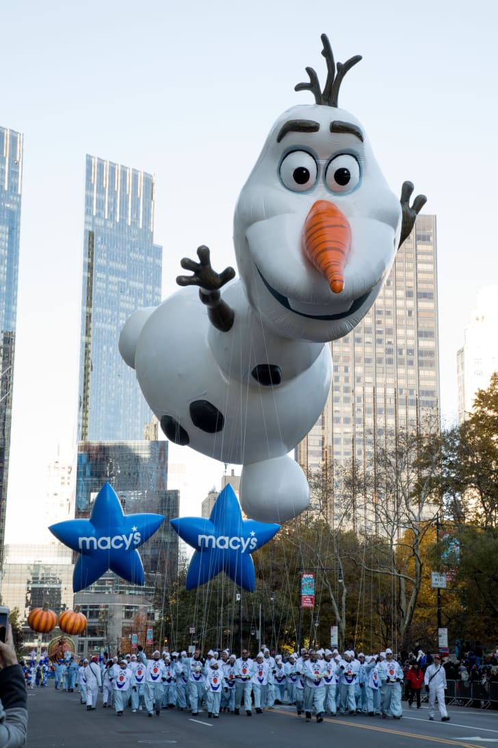 Balloon handlers float Olaf down Central Park South during the annual Macy's Thanksgiving Day Parade.