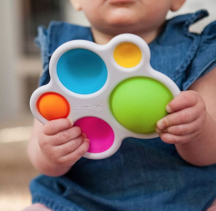 A young child plays with the Fat Brain Toys Dimpl Baby and Toddler Learning Toy