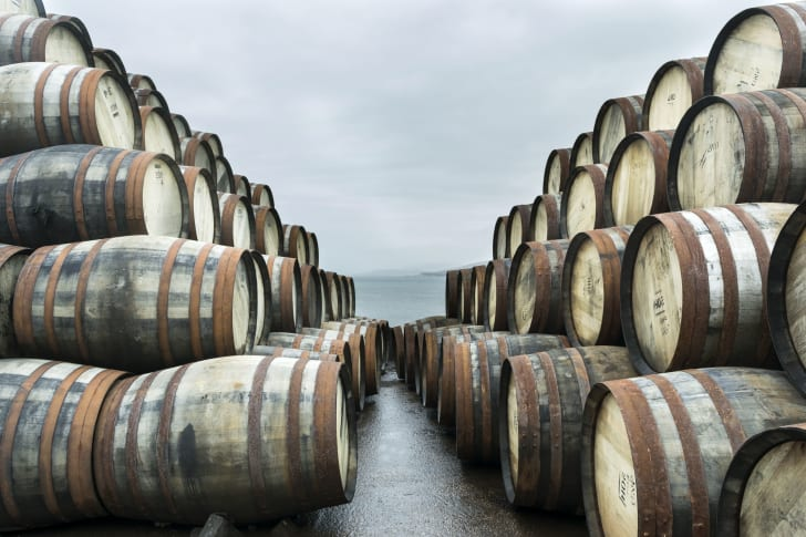 Many barrels stacked on a dock with the water in the background