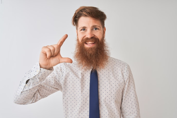 A redheaded man with a big beard gestures a size with his fingers