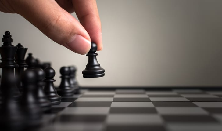 A hand moves a black pawn forward on a chess board