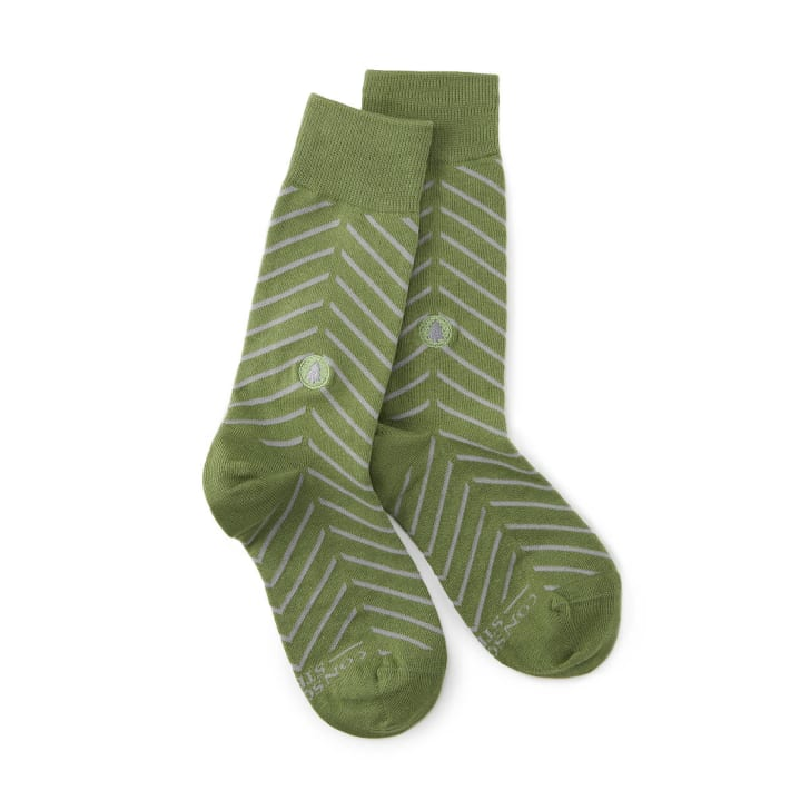 Image of a pair of green socks with thin gray stripes. In the center, there is a green embroidered circle, about the size of a quarter, with a gray tree silhouette in the center.
