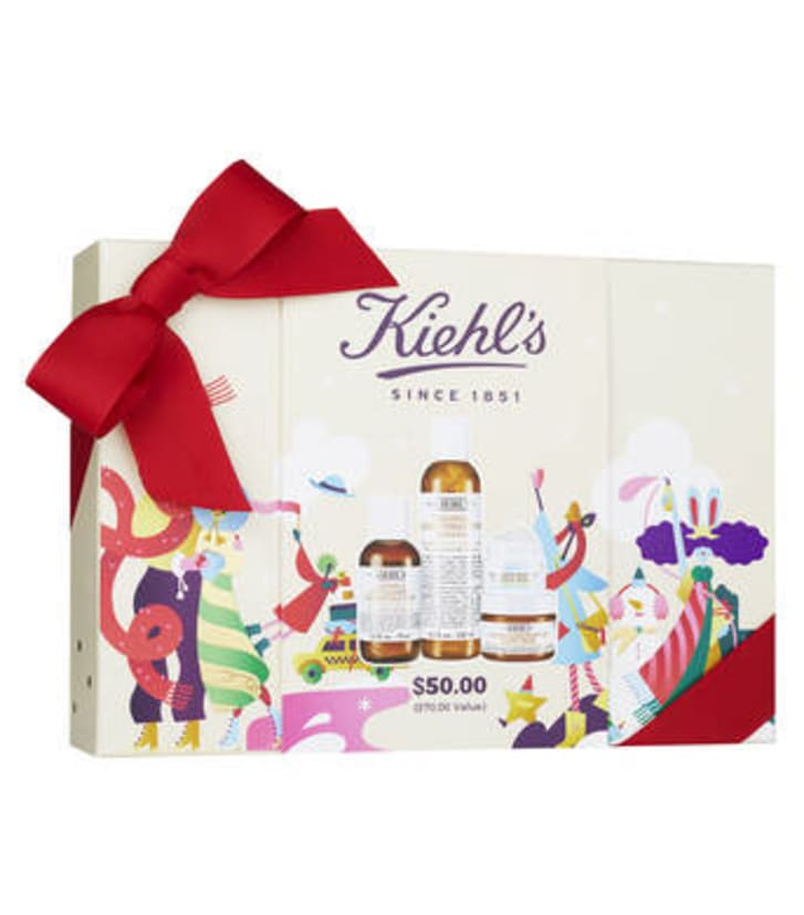 Image of a box of skin care products with the Kiehl's logo on the front. There is a red bow tied on to the upper left corner of the box.