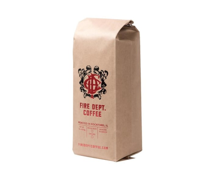 Image of a brown paper bag full of ground dark roast coffee. The bag bears the label for Fire Dept. Coffee.