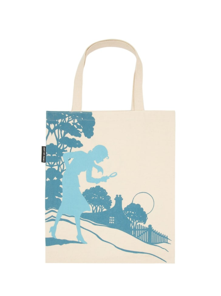 Image of a beige colored tote bag with dark blue details of a scene with trees and a house. In the foreground, in a lighter blue color, is a girl with a braid holding a magnifying glass.