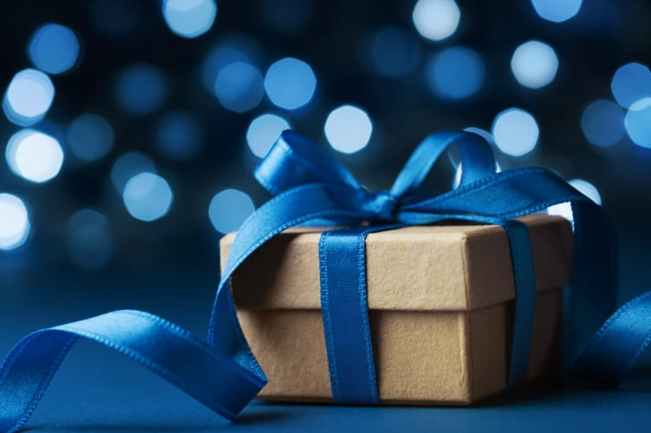A small gift in a brown box with a blue ribbon in a bow around it.