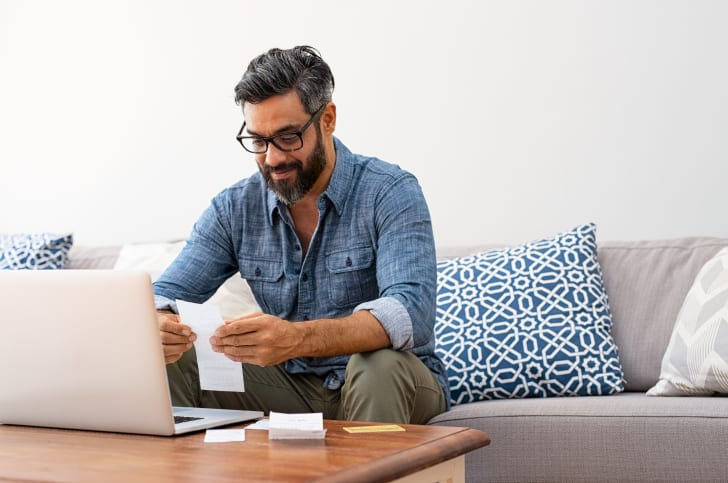 A person sitting in front of a computer with receipts.