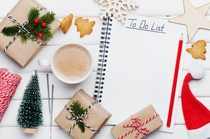 """A notebook with """"To Do List"""" written in it on a table with Christmas presents, decorations, and cookies."""
