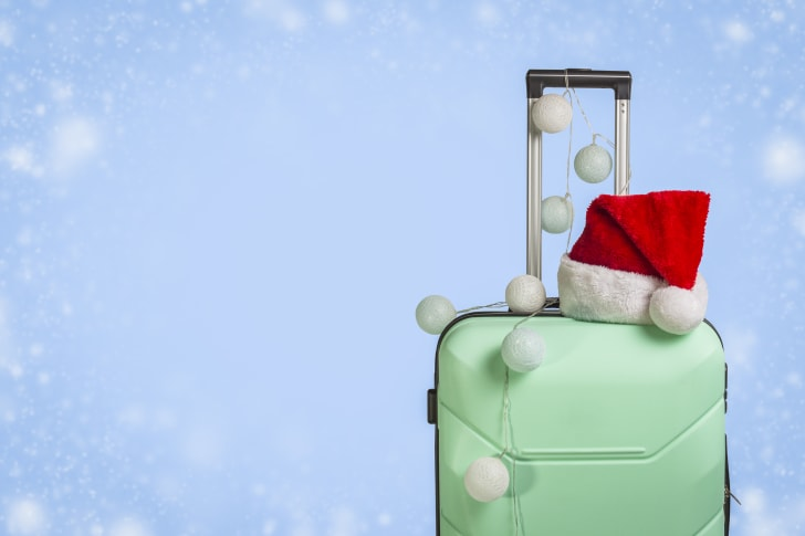 A green suitcase with a santa hat on top, on a blue background.