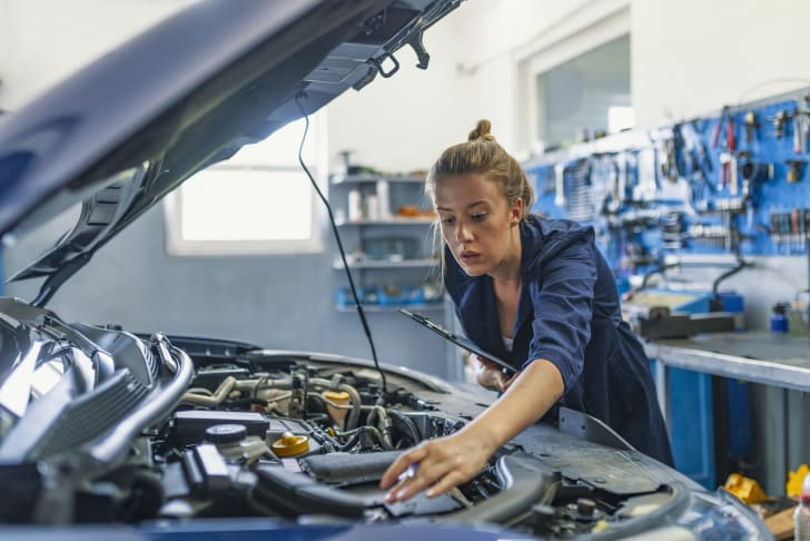 A mechanic adjusts something under the hood of a car.