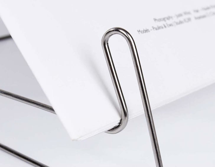 A foldable metal book stand holding paper