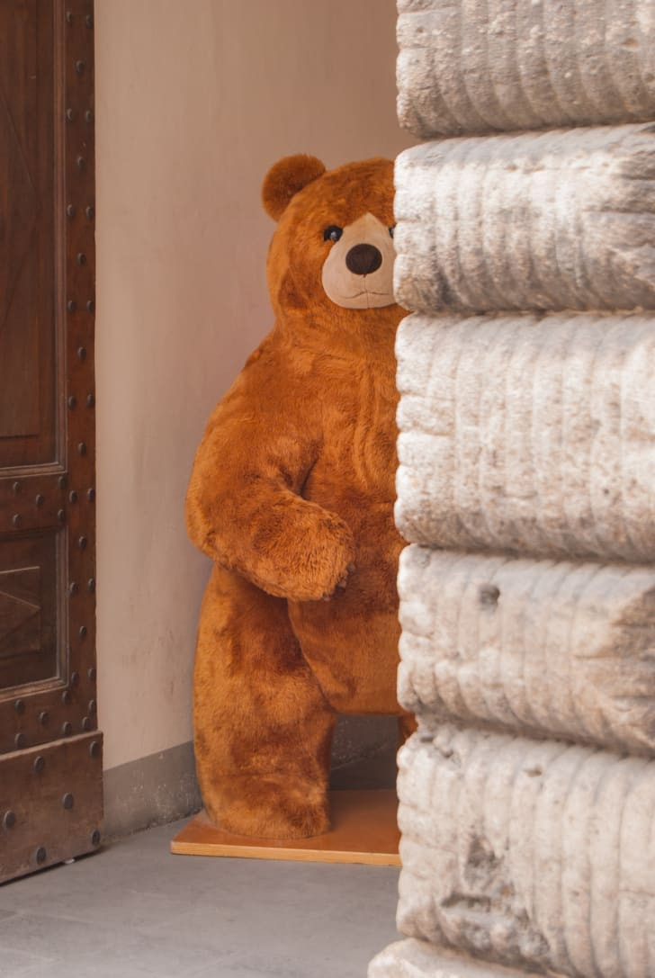 A big teddy bear peeking out from behind a wall.