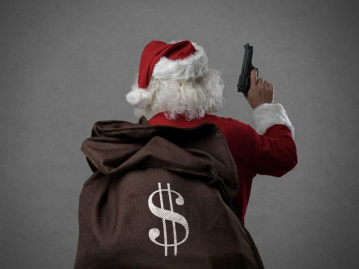 A man dressed as Santa Claus is pictured holding a gun and a sack of money
