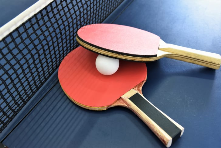 Close up of table tennis paddles and ball on a table near the net