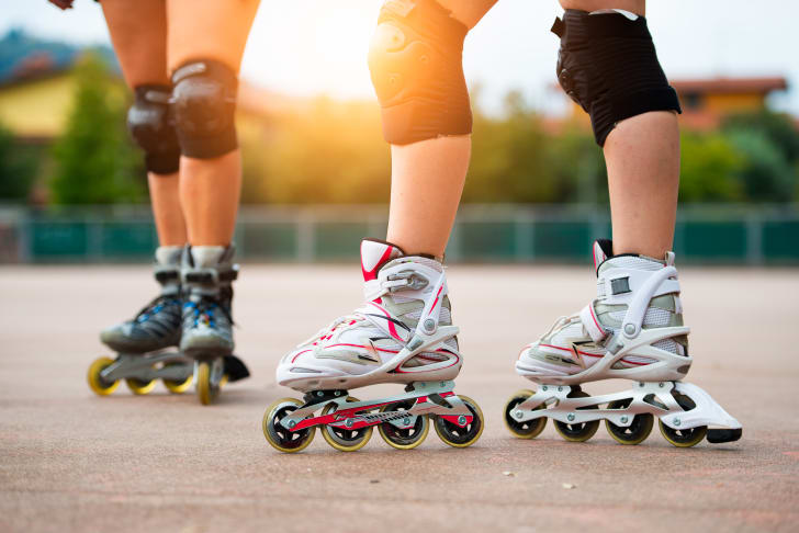 Two sets people's legs, wearing knee pads and roller blades