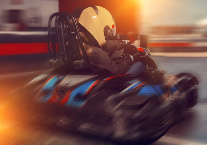 A girl in a helmet driving a go-kart