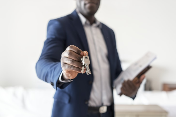 A man holding a set of keys and papers