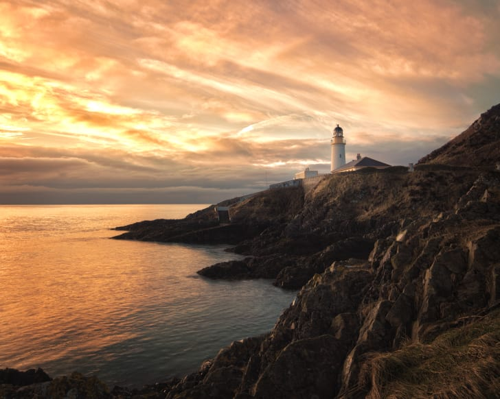 Sunrise on the rocky coast of the Isle of Man with a lighthouse