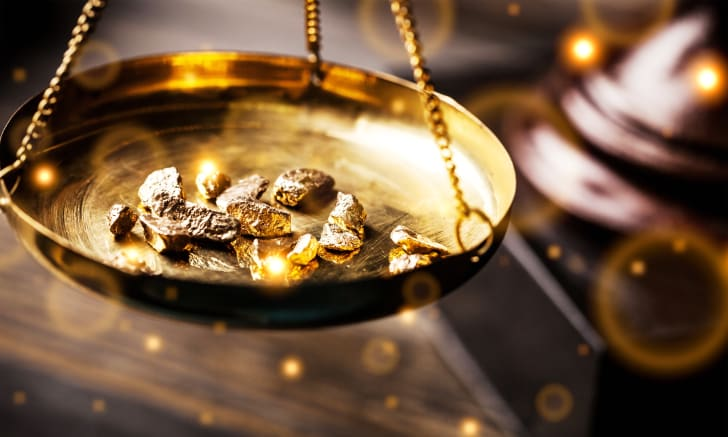 Nuggets of gold weighed on a golden scale platform