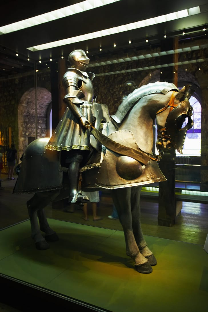 A large set of full Medieval armor displayed on an armored stuffed horse