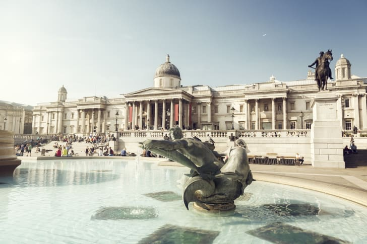 A fountain in front of a large columned building on Trafalgar Square