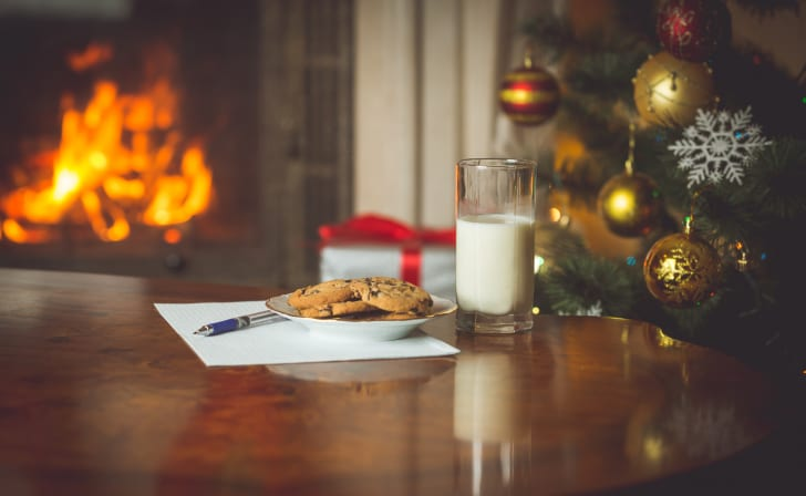 Closeup image of wish list and treats for Santa Claus on table next to burning fireplace