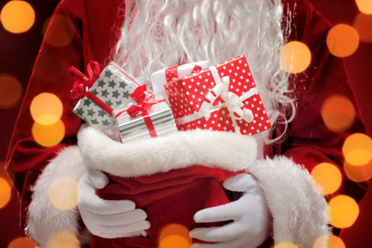 A man dressed as Santa Claus is pictured holding up a bag of gifts