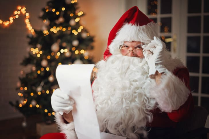 A man dressed as Santa Claus is pictured reading a piece of paper