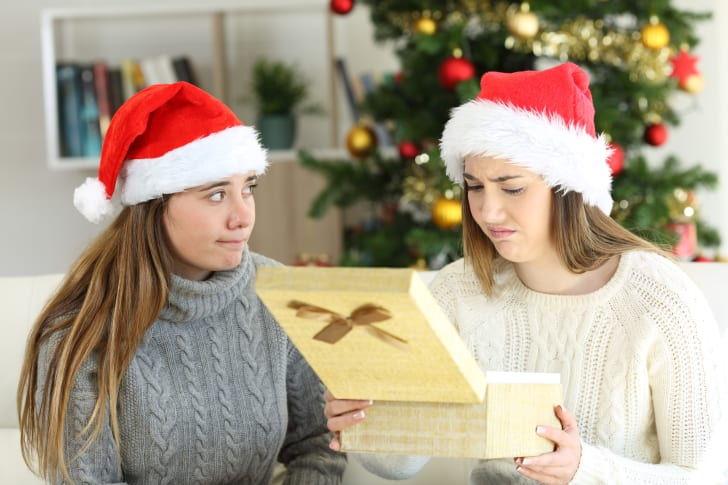 Two women wearing Santa hats open up a gift that one of the women doesn't like.