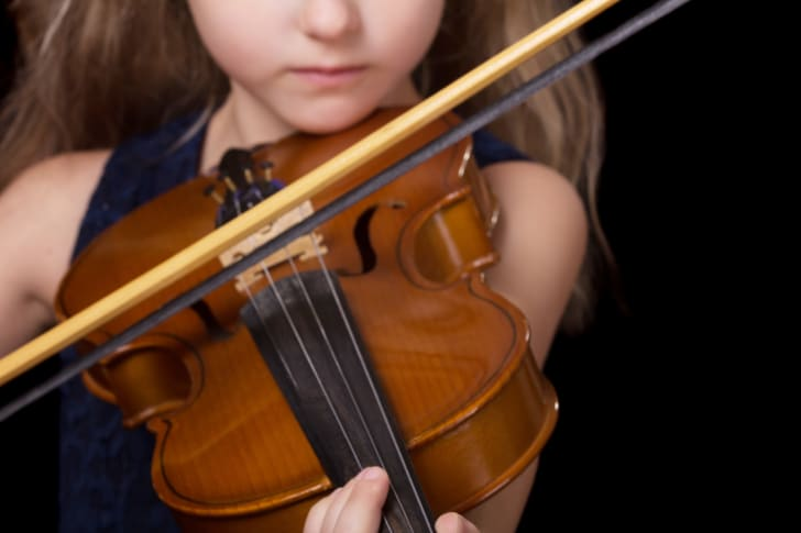 A young girl playing the violin.