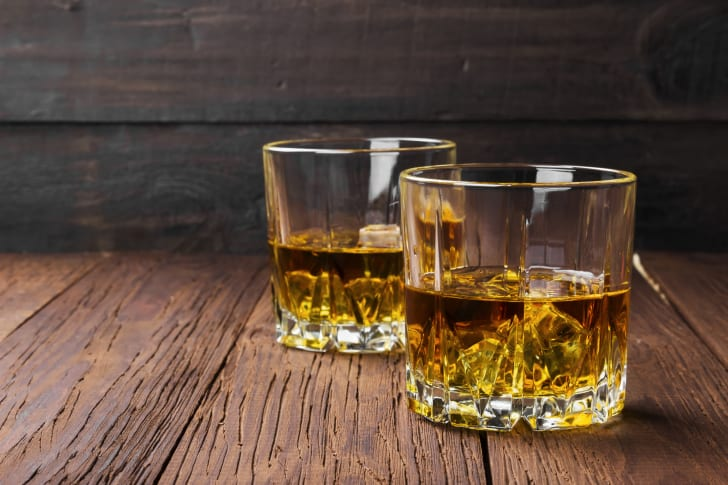 Two glasses of whiskey on a wooden table.