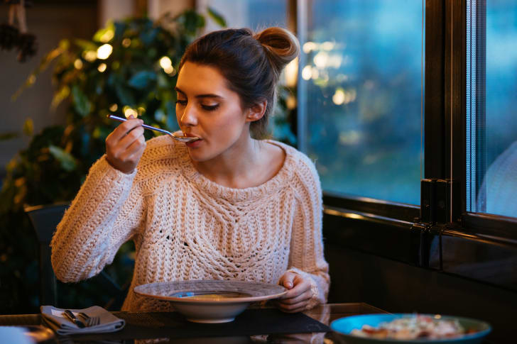 Woman in a cafe eating hot soup