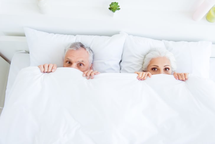 A gray-haired man and gray-haired woman peep out from underneath bed covers