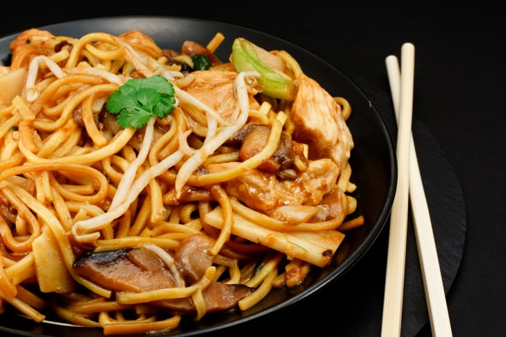 A plate of chow mein noodles and chopsticks