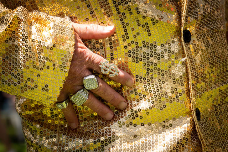 A close up of a gold sequined jacket on a man with three golden rings on his fingers