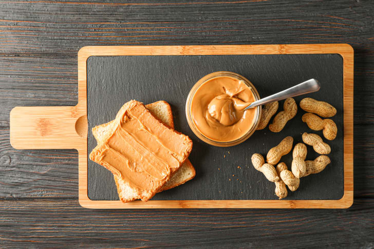 Glass jar with peanut butter and spoon, peanut, peanut butter sandwich and cutting board on wooden background
