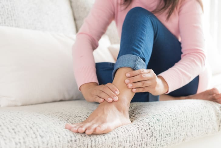 Photo of a young woman sitting on the sofa massaging her ankle and foot