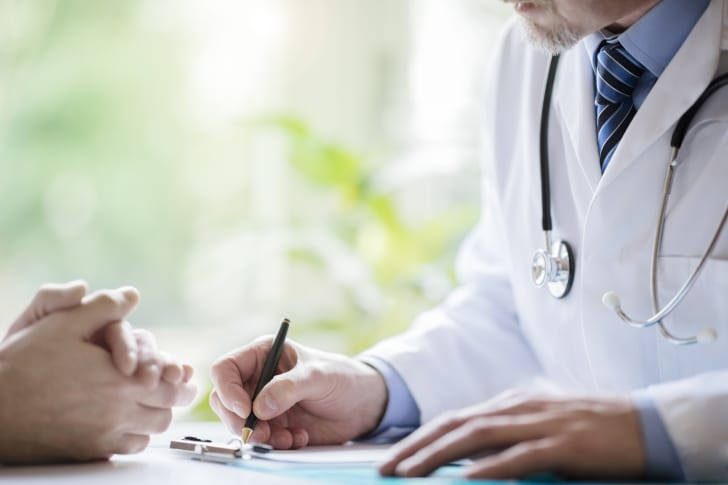 Photo of a doctor taking notes while meeting with patient