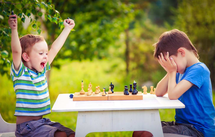 A young boy celebrates as another young boy buries his head in his hands across a chess board