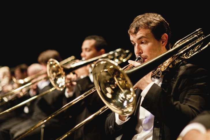 Close up of a trombonist in a line of men playing trombones