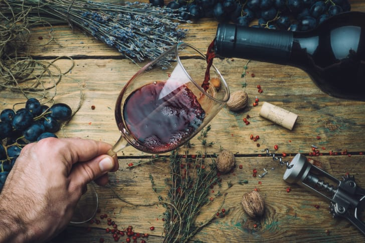A hand pours a bottle of red wine into a glass