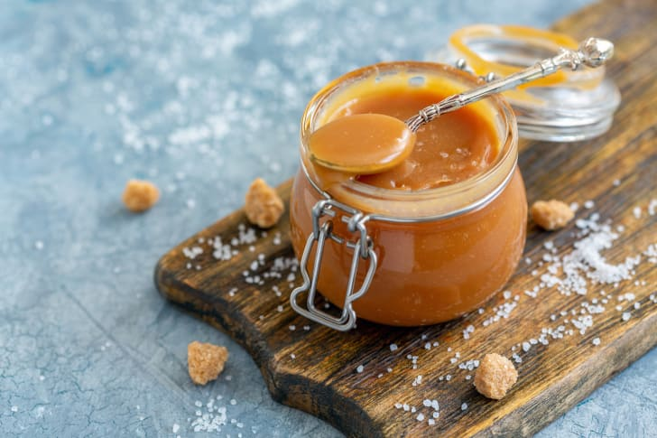 A spoon resting on top of a small jar of caramel