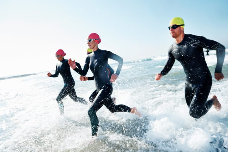 Athletes run through the water during a triathlon