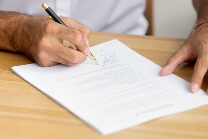 A man signs a business document